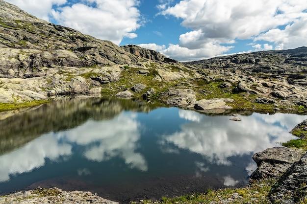 Озерный пейзаж с отражением облаков, скалистая горная тундра, дорога к скале тролльтунга