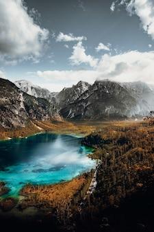 Lago in mezzo alle montagne sotto nuvole bianche e cielo blu durante il giorno