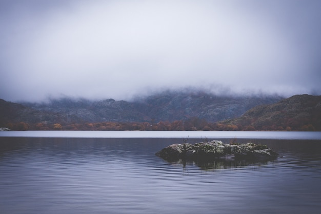 Lake between mountains with low clouds