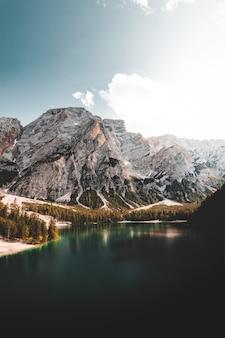 Озеро возле горы под голубым небом в дневное время