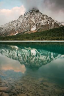 Озеро у горы под белым небом в дневное время новое фото
