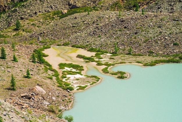 늪지 지형으로 산의 돌 사면 근처 오래 된 청록색 호수. 희미한 습지 색상의 매끄러운 물 표면. 하얀 모래. 알타이 자연의 특이한 풍경.