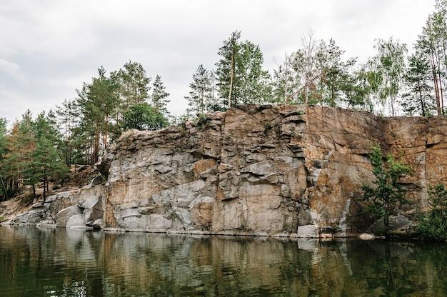 Озеро на фоне скал и елей