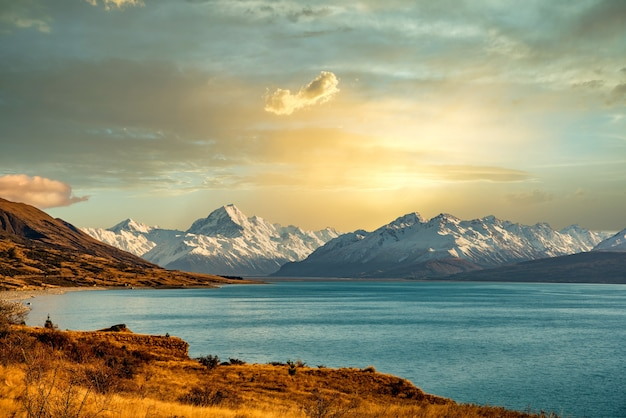 Облачный пейзаж озера пукаки с горой аораки кук и южными альпами в сумерках