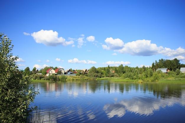 Озеро, отражающее небо с облаками, протекает через небольшую деревню и покрывает берега деревьями, кустарниками и растущими на них растениями.