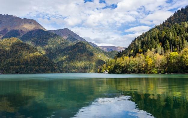 Озеро рица в абхазии осенью, вид на озеро с осенним лесом на заднем плане