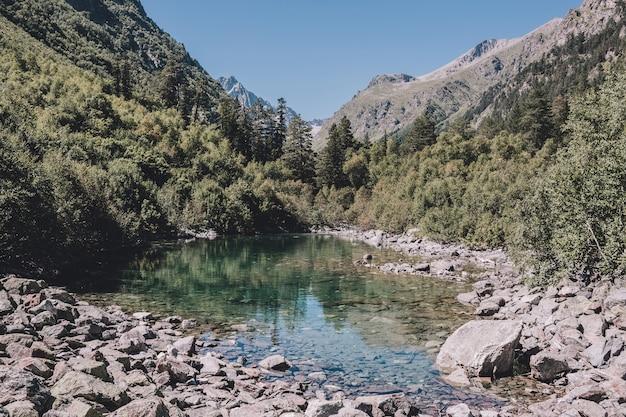 山の湖のシーン、国立公園ドンバイ、コーカサス、ロシア、ヨーロッパ。サンシャインの天気、青い空、遠くの緑の木々。カラフルな夏の日、時間