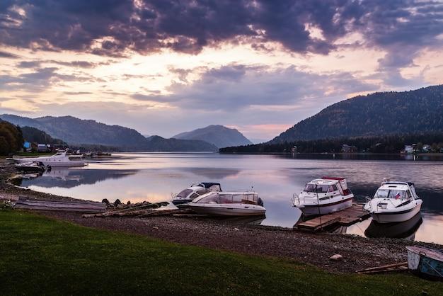夜明けに係留されたモーターボートのある湖岸テレツコイェ湖アルティバシュ村アルタイロシア