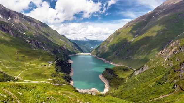 오스트리아 카 프룬 고산 저수지의 언덕과 녹지로 둘러싸인 호수