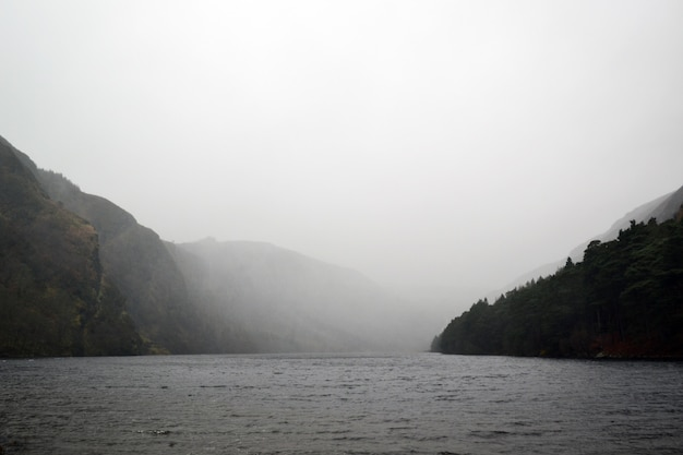 Lake surrounded by hills under the foggy grey sky