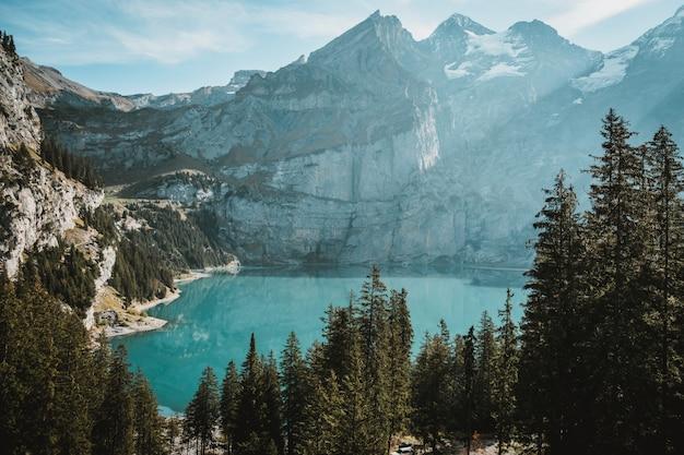 Озеро в окружении скал, покрытых снегом, и лесов под солнечным светом