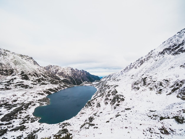 Lake surrounded by the tatra mountains covered in the snow in poland