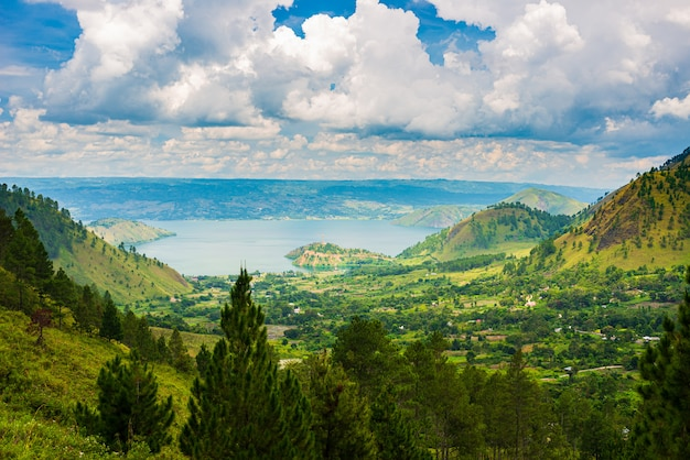 Lake toba and samosir island view from above sumatra indonesia. huge volcanic caldera covered by water, green rice paddies, equatorial forest.