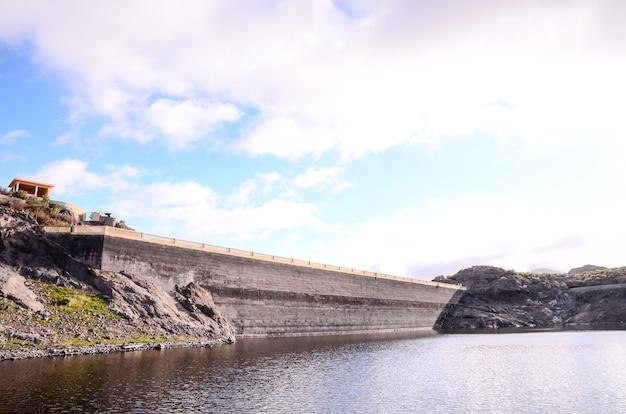 曇った青い空とカナリア諸島の湖の水ダム
