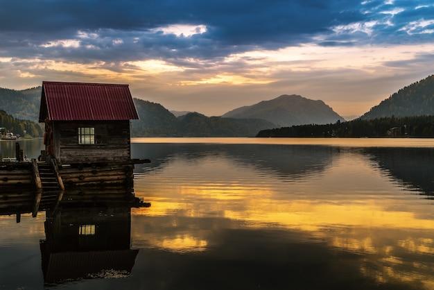 夜明けに木製の桟橋がある湖埠頭。テレツコイェ湖、アルティバシュ村、アルタイ共和国、ロシア