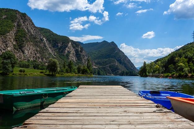 Озеро с каноэ, горы и лес в пасмурный день.