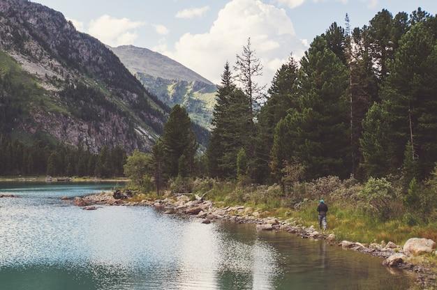 바위 능선이 있는 호수. 아름다운 풍경. 관광객은 호수 기슭에 있는 바위 위로 갑니다. 알타이 러시아.