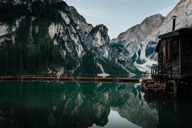 Озеро с деревянными лодками и отражение горы