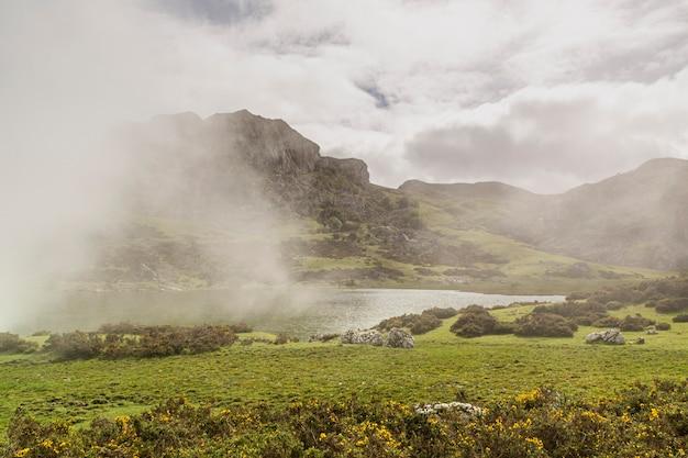 春に霧が発生するコバドンガの湖。エノル湖でハイキングする観光客。スペイン、アストゥリアス