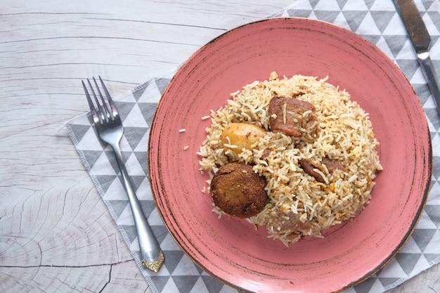Еда ягненка бирьяни в тарелку на стол.