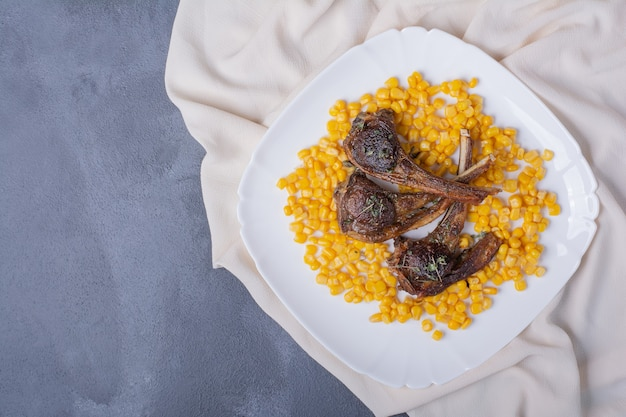 Lamb chomps on white plate with boiled corns and sateen tablecloth on blue.