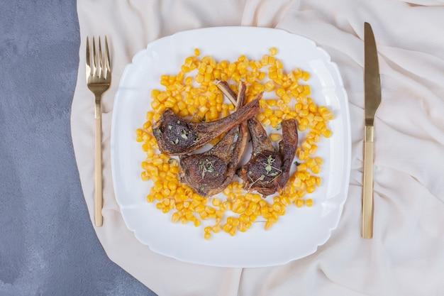 Agnello chomps sul piatto bianco con semi bolliti e tovaglia in raso sul blu.