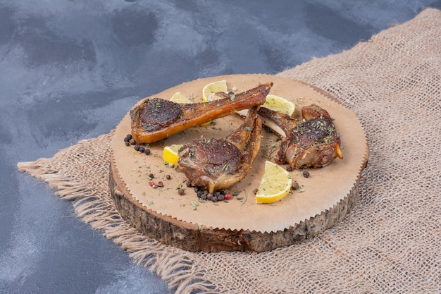 Lamb chomps on wooden board with lemon slices and cutlery on tablecloth.
