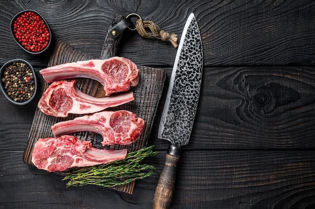 Баранина нарезает сырое мясо на кости с солью, перцем и зеленью. черный деревянный фон. вид сверху. скопируйте пространство.