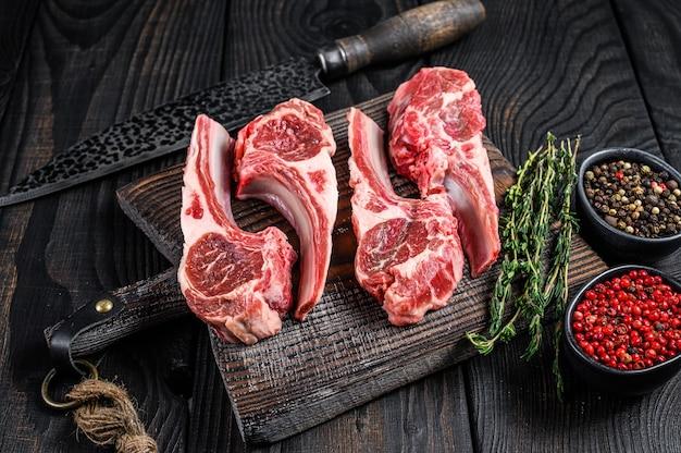 Баранина нарезает сырое мясо на кости с солью, перцем и зеленью. черный деревянный фон. вид сверху.