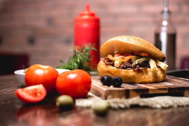 Lamb doner in bread with cucumber pickles fries tomato served with ketchup and mayonnaise