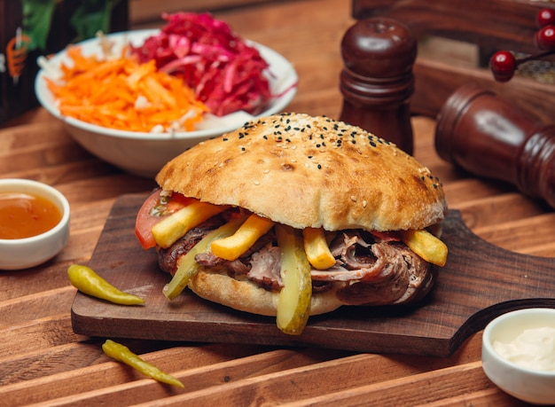 Lamb doner slices with french fries, pickled cucumber, tomato in pita bread