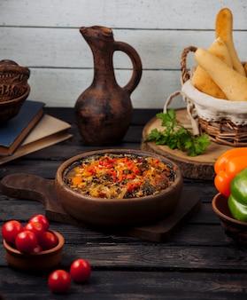 Шашлык из баранины жареный с луком, помидорами и сладким перцем в глиняной сковороде
