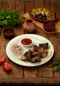 Lamb kebab served with onion and sumac blend, tomato and herbs sauce