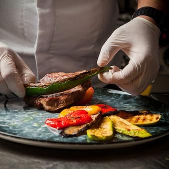 Kebab di agnello con verdure fritte e mano umana nel piatto rotondo