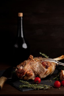 Lamb leg with herbs and bottle of red wine
