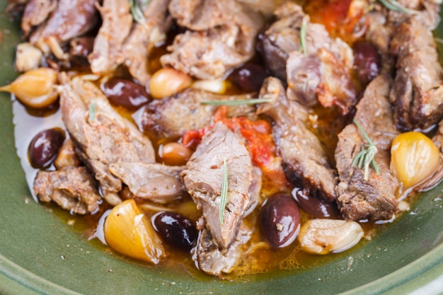 Lamb meat cooked in a tagine with olives, garlic, lemon and rosemary.