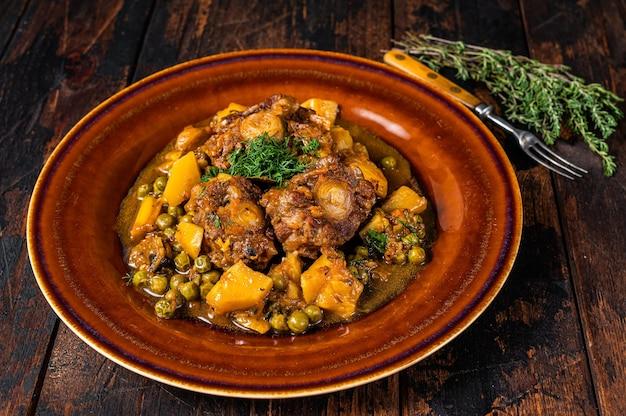 Рагу из баранины из бычьих хвостов с овощами в деревенской тарелке