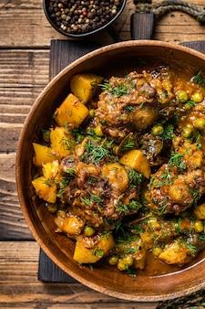 Бычьи хвосты ягненка тушат с овощами в деревянной тарелке. деревянный фон. вид сверху.