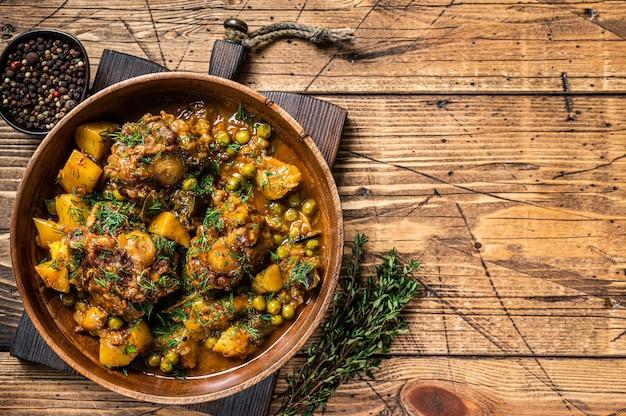 Тушеные хвосты баранины с овощами в деревянной тарелке