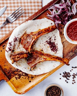 Lamb ribs kebab with red onions on a wooden board