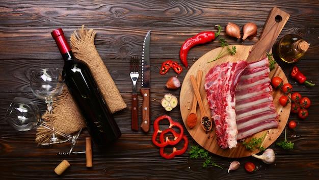 Бараньи ребрышки со специями и овощами и бутылка красного вина