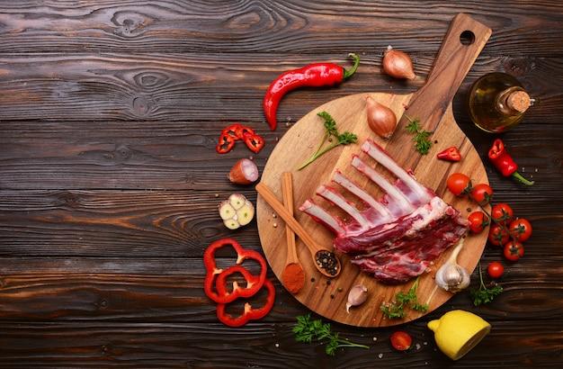 Ребрышки ягненка со специями и овощами на деревянном пространстве