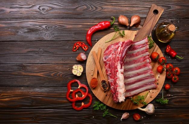 Ребра ягненка со специями и овощами на деревянной поверхности
