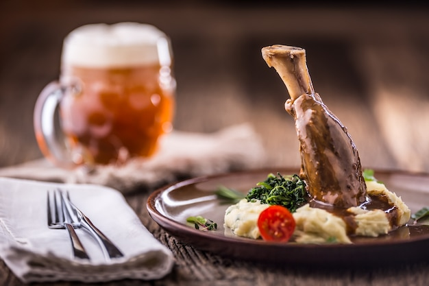 Lamb shank.confit lamb shank with mashed potatoes spinach and draft beer in pub or restaurant.