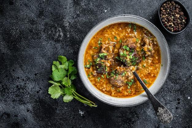 양고기 수프 kharcho는 양고기, 쌀, 토마토, 향신료를 그릇에 담고 있습니다. 검은 배경. 평면도. 공간을 복사합니다.