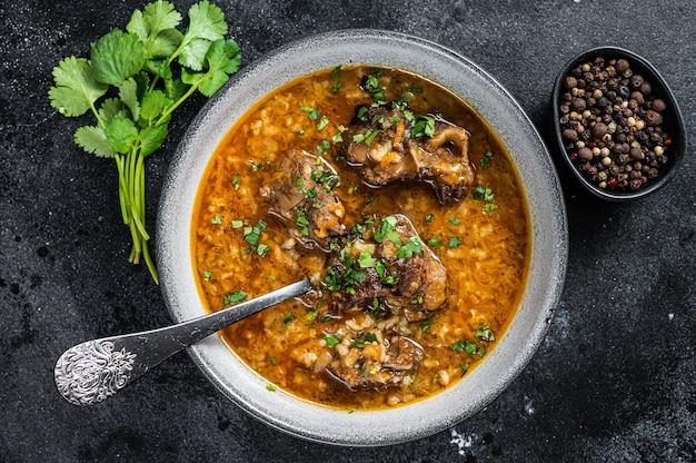 Суп из баранины харчо с бараниной, рисом, помидорами и специями в миске. чернить