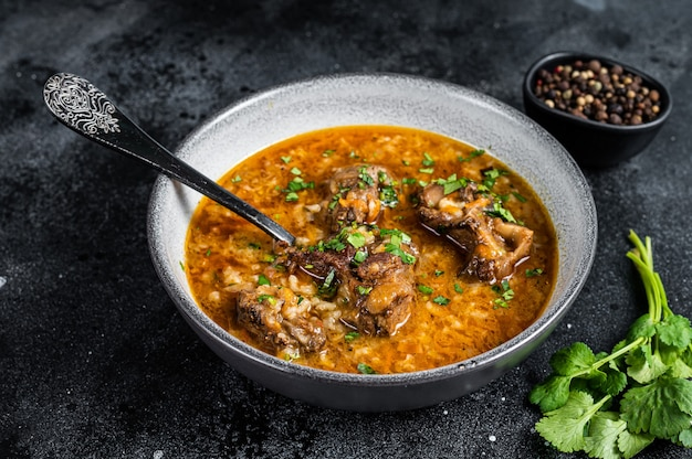 Lamb soup kharcho with mutton meat, rice, tomatoes and spices in a bowl. black background. top view.