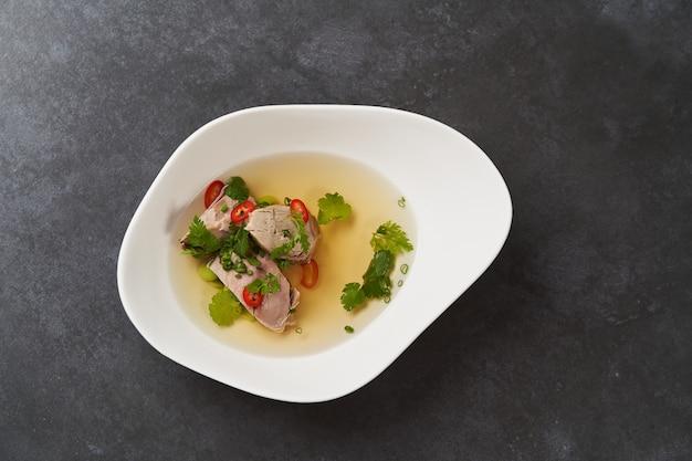 唐辛子、トマト、パセリ、豆の白いボウルの子羊のスープ