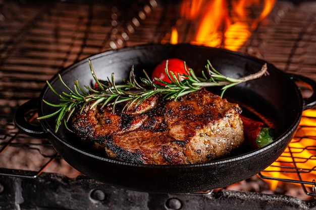Lamb steak is fried on a fire in a cast iron pan
