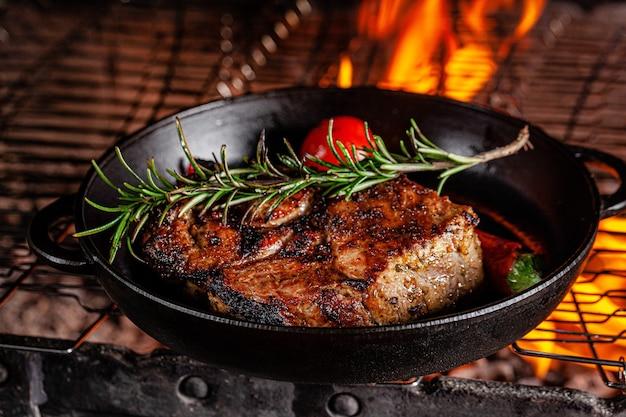 Стейк из баранины обжаривается на огне на чугунной сковороде